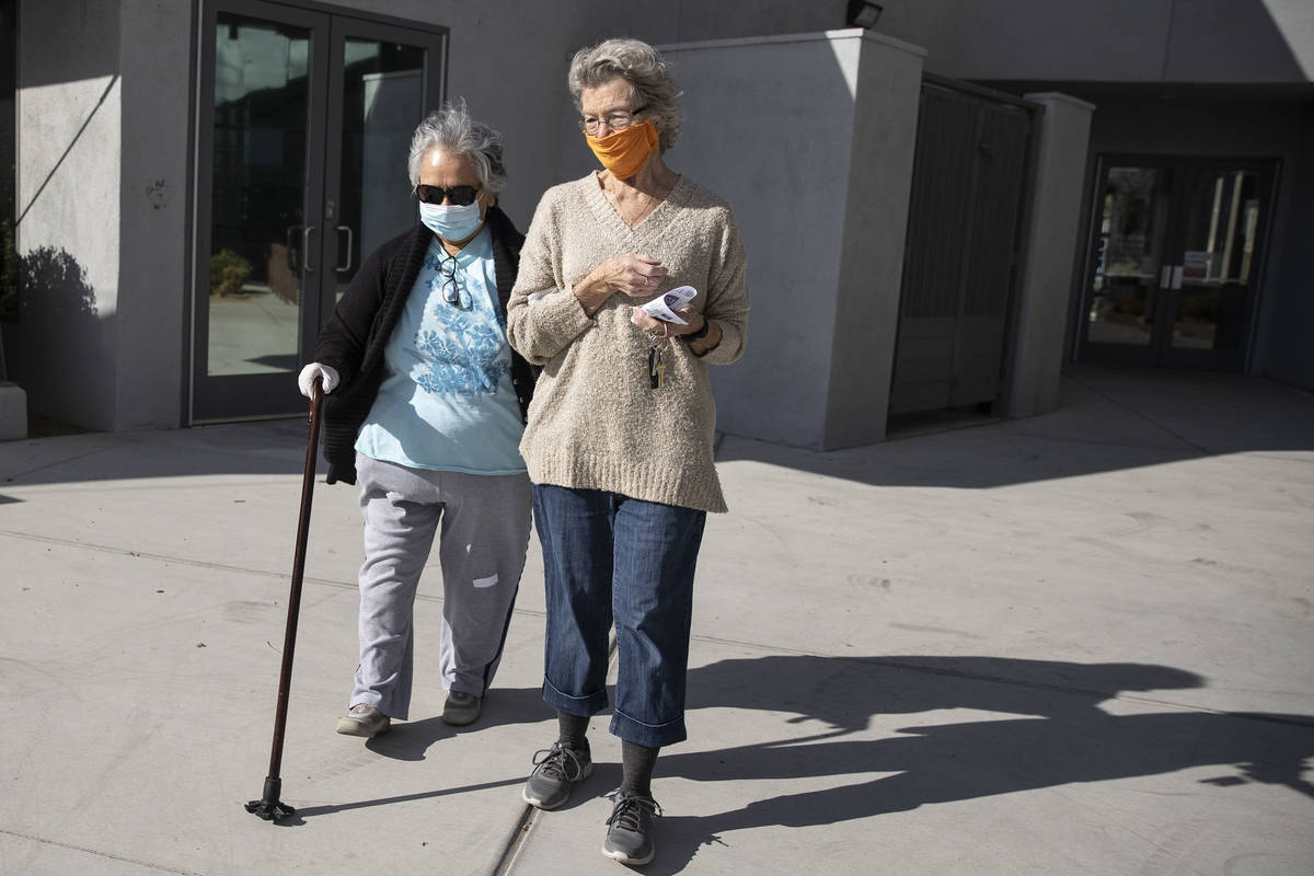 Carmen Mathis, 80, left, is assisted to her car by her friend Gail Smith, 81, after getting the ...