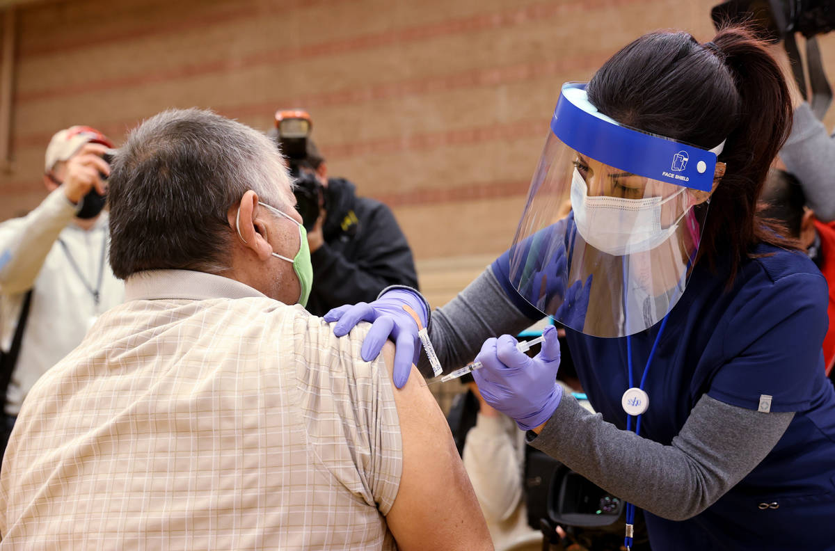 Daliah Rubio, a registered nurse with Southern Nevada Health District, vaccinates Victor Rodrig ...