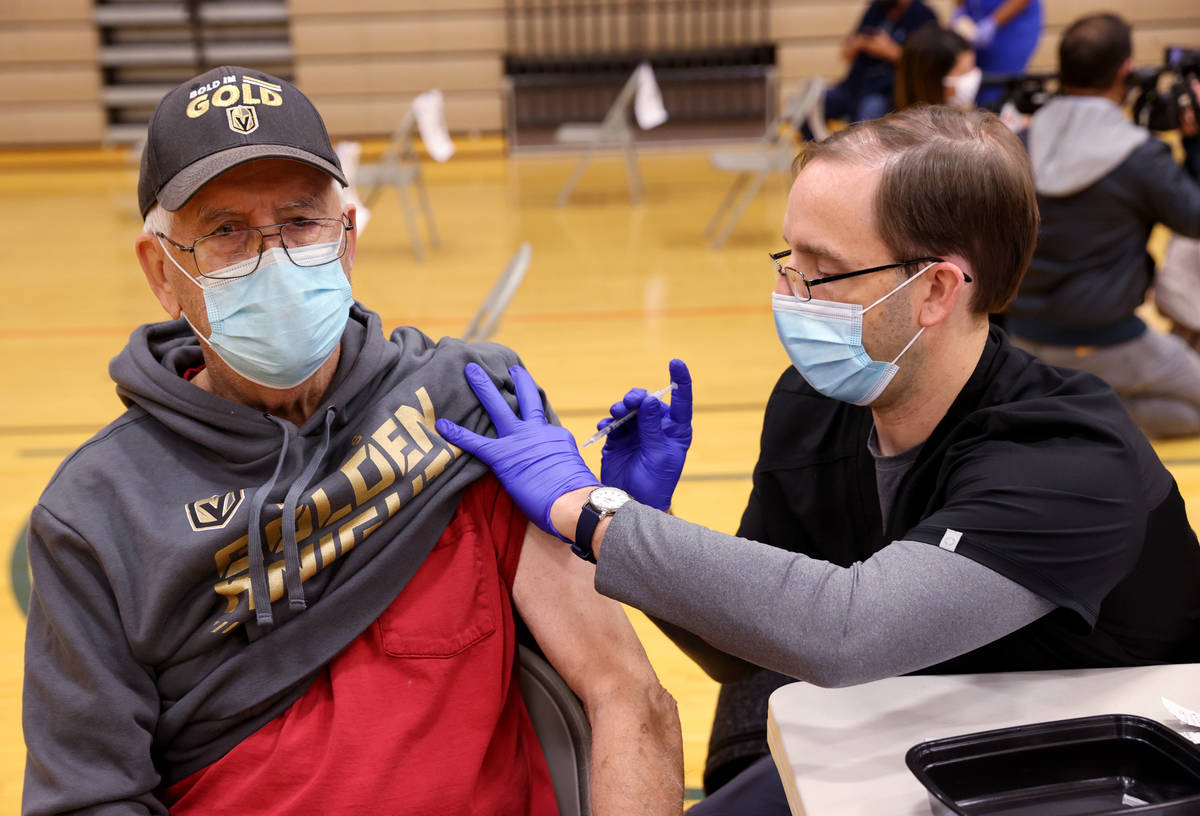 John Reynolds, a registered nurse with Southern Nevada Health District, vaccinates Bill Henning ...
