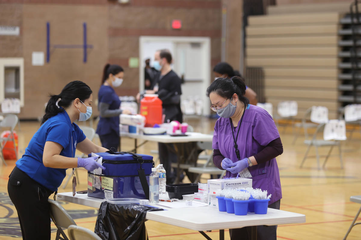 Southern Nevada Health District workers prepare for a COVID-19 pop-up vaccination clinic at Mac ...