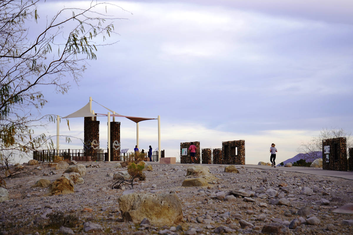 Runners and walkers head up to Sunset Park's Dune Overlook, a perch that allows views across ...