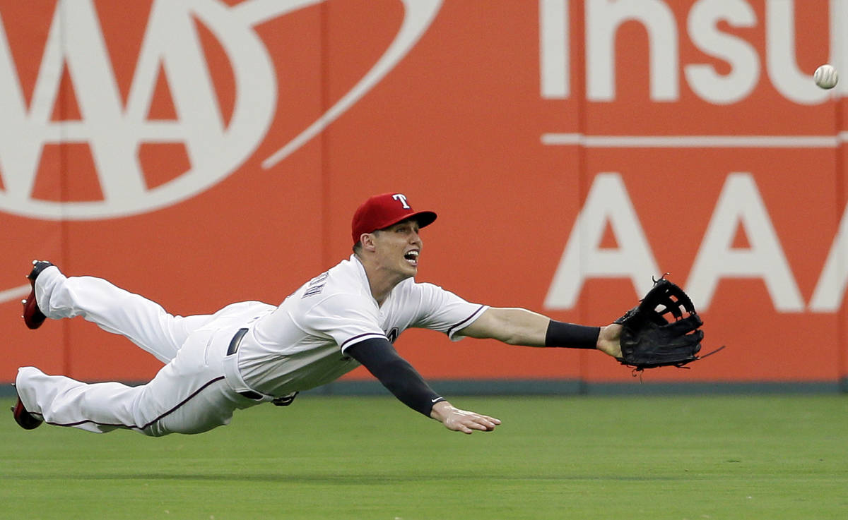 Texas Rangers center fielder Drew Robinson leaps to catch a fly-out by Detroit Tigers' John Hic ...