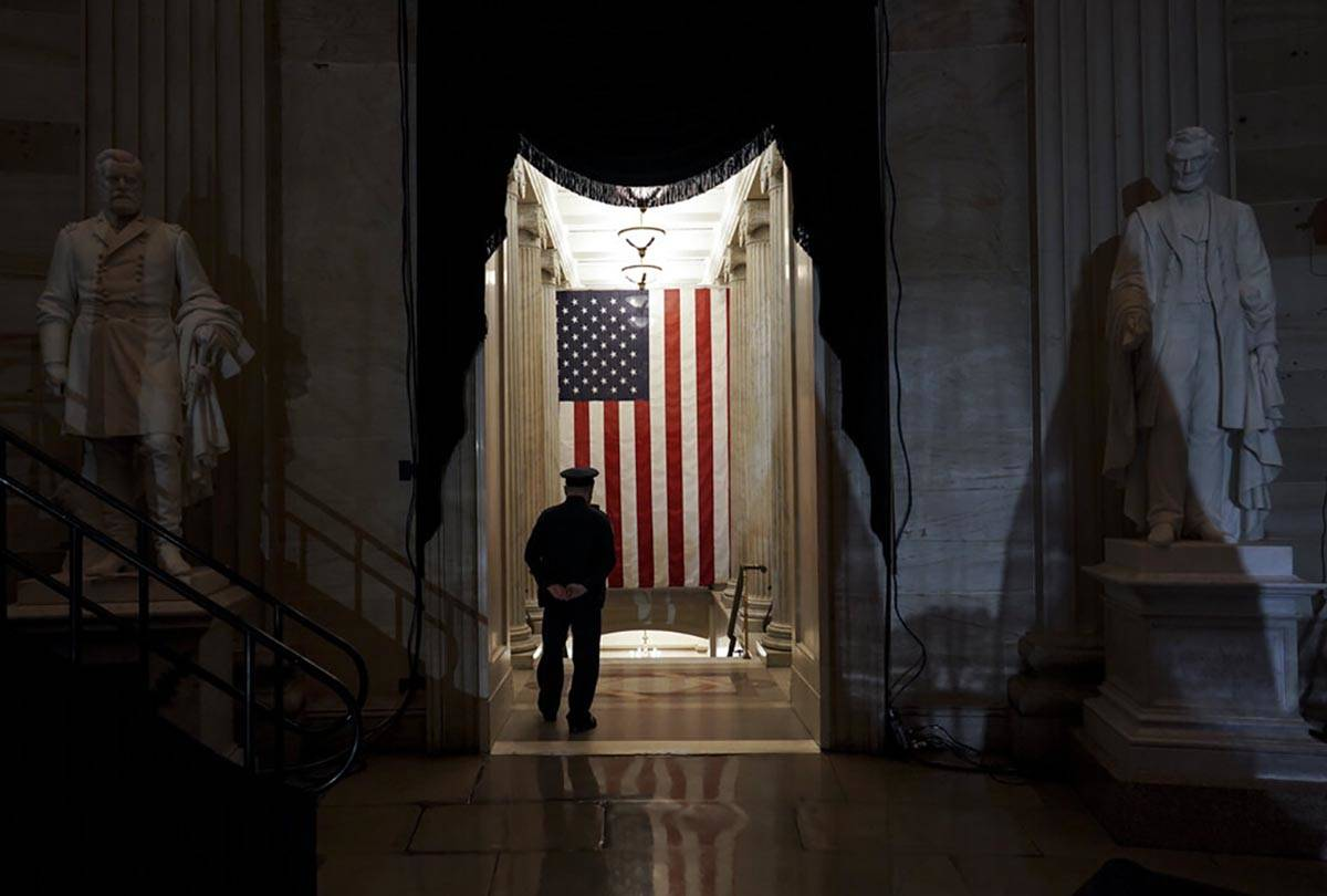 A U.S. Capitol Police officer stands at the door of the Capitol Rotunda near where the late U.S ...