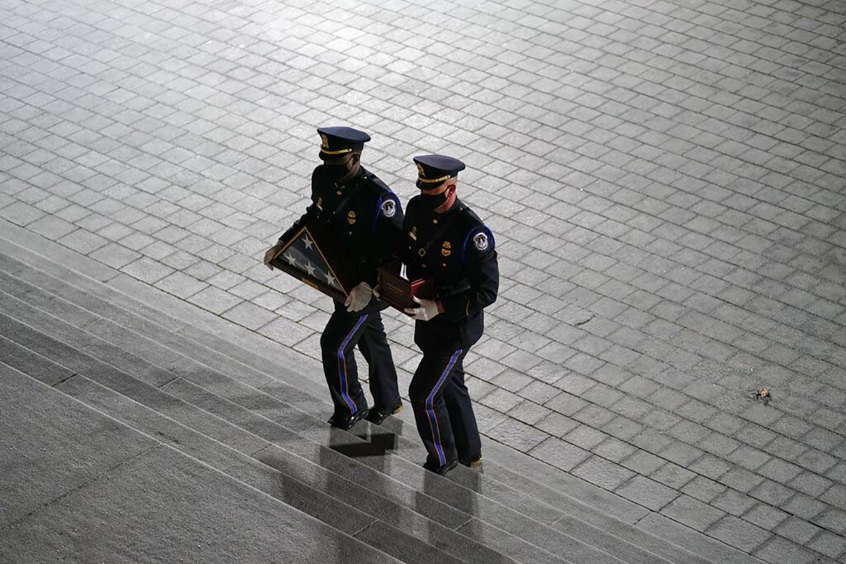 An honor guard carries an urn with the cremated remains of U.S. Capitol Police officer Brian Si ...