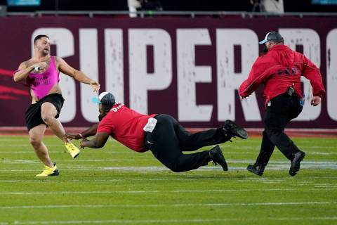 Security tries to grab a fan on the field during the second half of the NFL Super Bowl 55 footb ...