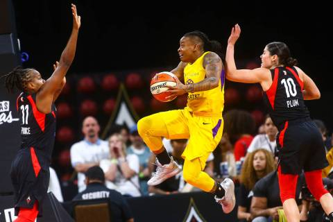 Los Angeles Sparks' guard Riquna Williams goes to the basket between Las Vegas Aces' Epiphanny ...