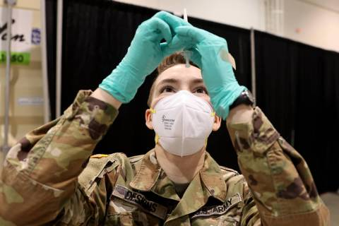 Nevada National Guard Spc. Katherine Deskins prepares to administer a Pfizer vaccine shot at th ...