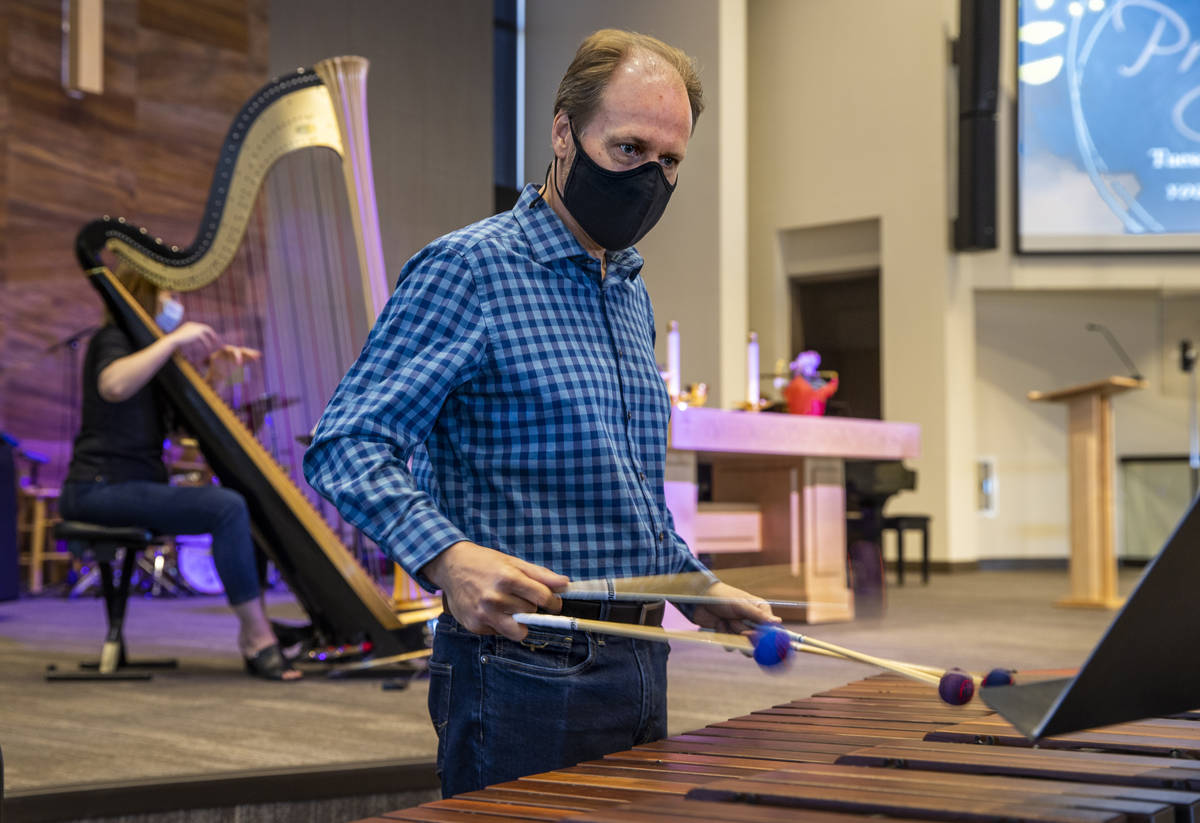Tim Jones plays the marimba as his wife, Melaney, plays the harp for an Ash Wednesday service a ...