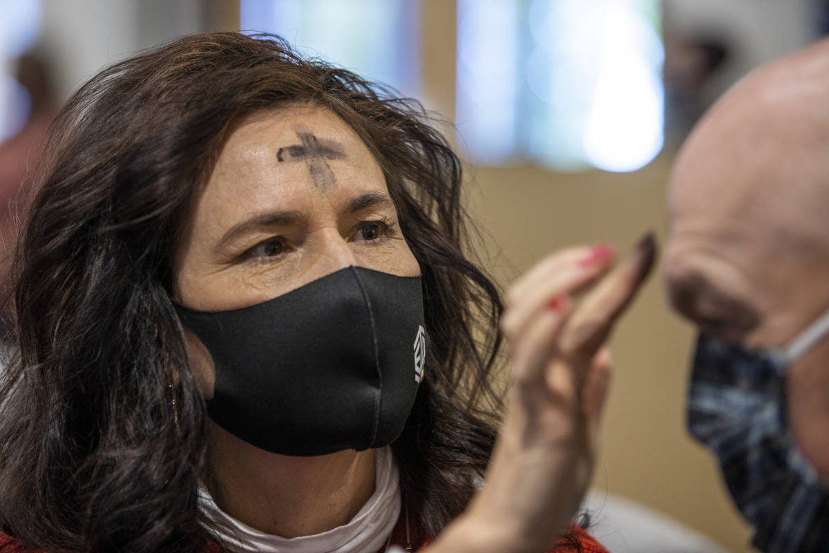 Shelley Flandermeyer places ashes in the sign of a cross on husband Matt's forehead during an A ...