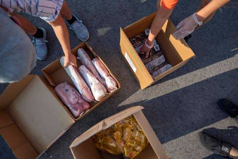 Three Square Food Bank volunteers grab frozen pork tenderloin, frozen blueberries and sack pack ...