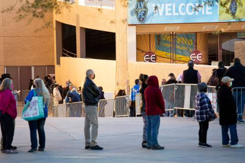 People wait in line for their COVID-19 vaccine at Cashman Field on Saturday, Feb. 20, 2021, in ...
