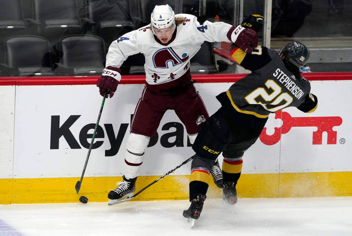 Colorado Avalanche defenseman Bowen Byram, left, fights for control of the puck with Vegas Gold ...