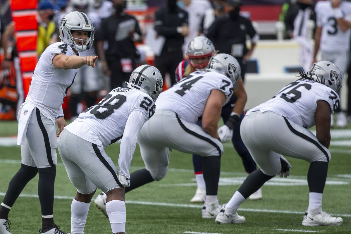 Las Vegas Raiders quarterback Derek Carr (4) calls a play at the line of scrimmage with running ...