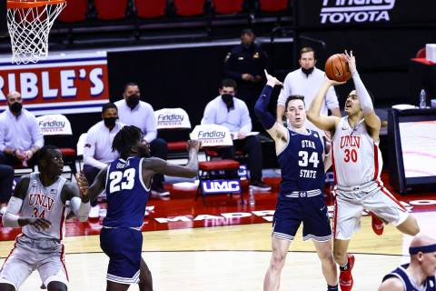 UNLV Rebels forward Devin Tillis (30) shoots over Utah State Aggies forward Justin Bean (34) du ...