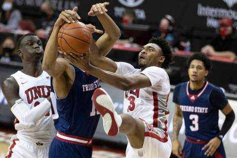 UNLV Rebels guard Bryce Hamilton (13) fight for a loose ball with Fresno State Bulldogs forward ...