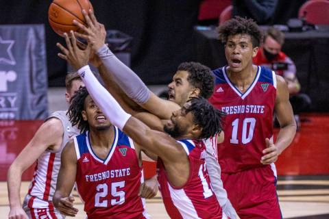 Fresno State Bulldogs guard Deon Stroud (13) and UNLV Rebels forward Devin Tillis (30) battle f ...