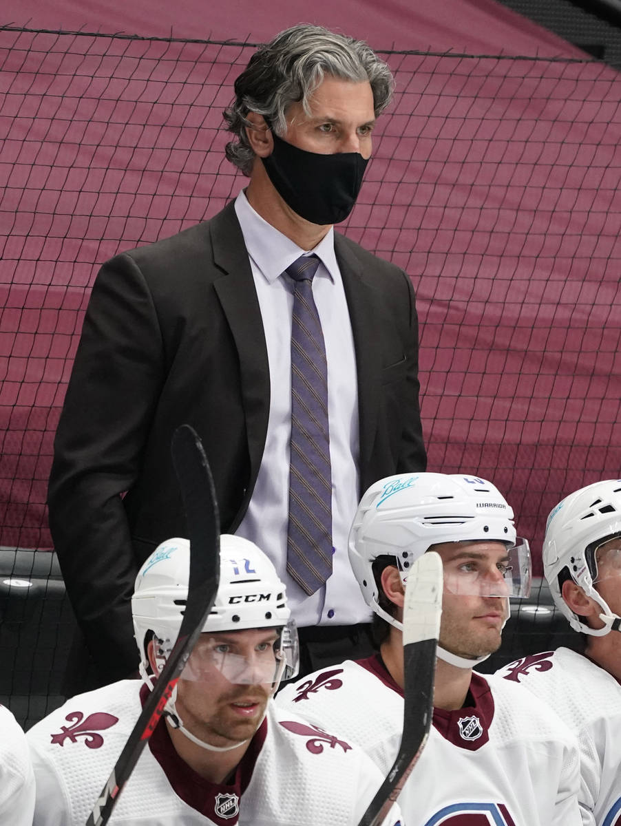 Colorado Avalanche head coach Jared Bednar, back, looks on in the third period of an NHL hockey ...