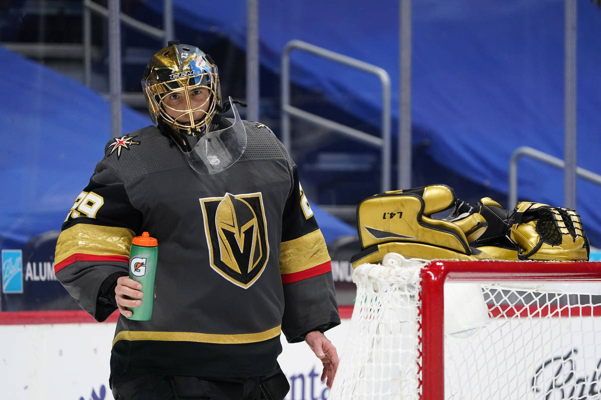Vegas Golden Knights goaltender Marc-Andre Fleury takes off his gloves and rests them on the to ...