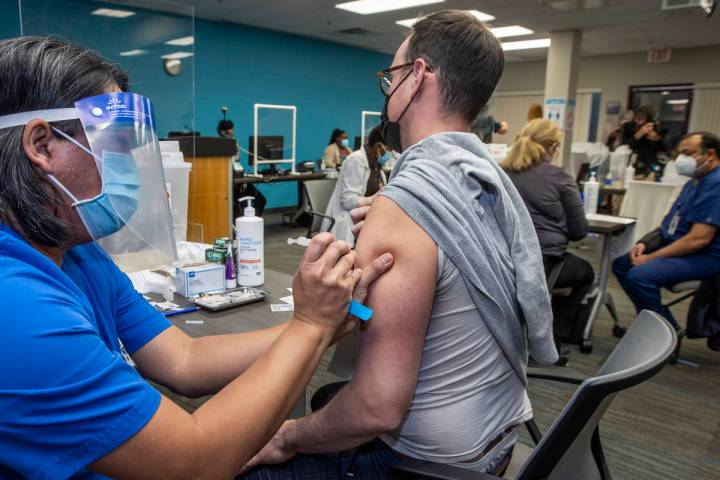 Noel Madic, RN, left, with the University Medical Center injects UMC resident physician Austin ...