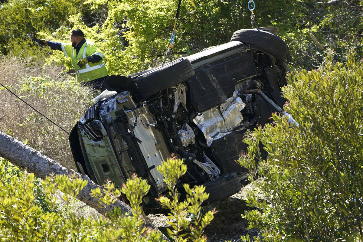 Workers move a vehicle on its side after a rollover accident involving golfer Tiger Woods Tuesd ...