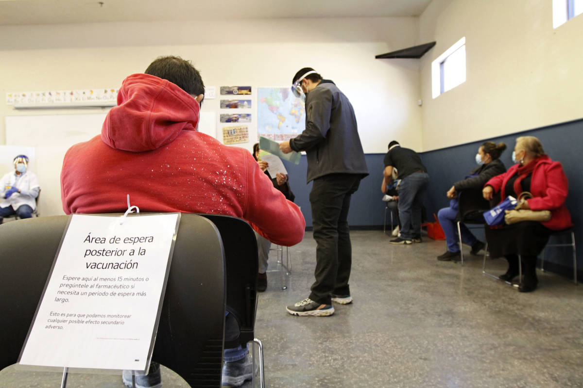 People wait a 15-minute observation period after receiving vaccine at Rafael Rivera Community C ...