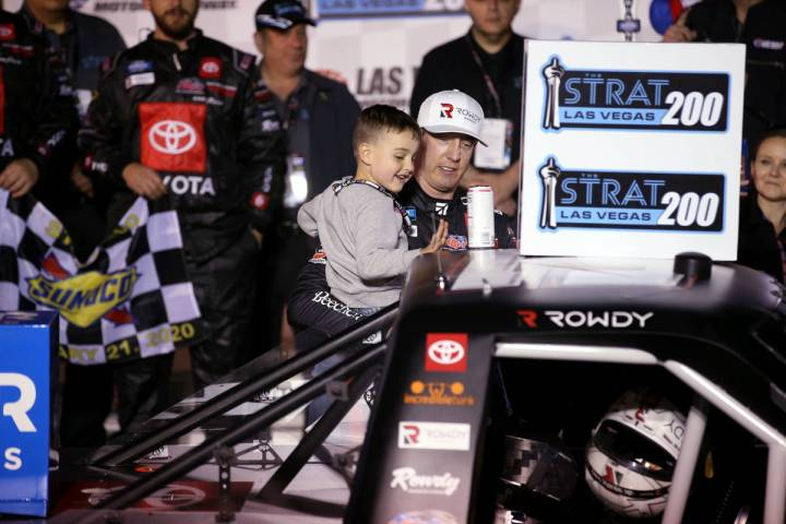 Kyle Busch and his son, Brexton, 4, apply the winner sticker to his truck after winning the Str ...