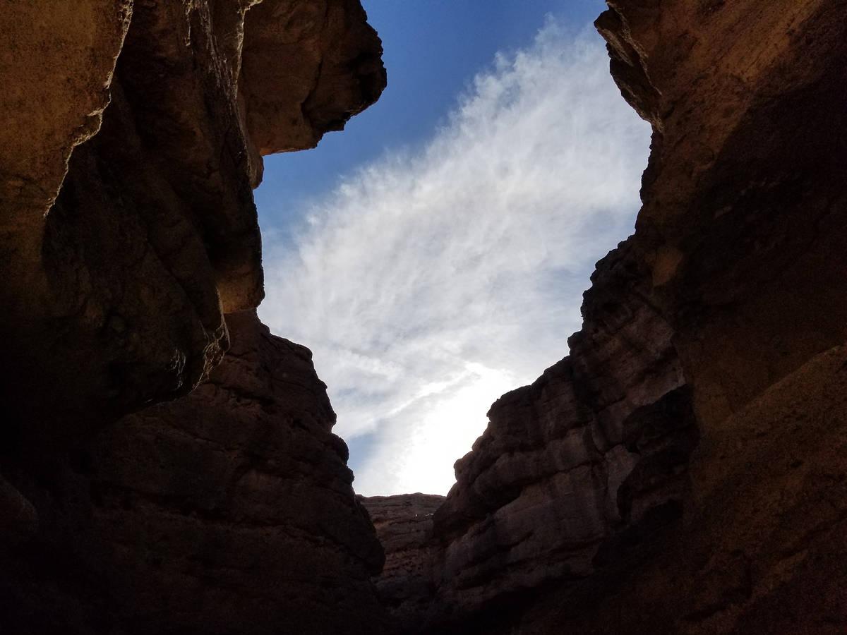 A large skylight of an opening between narrow rock walls inside the slot canyon. (Natalie Burt)