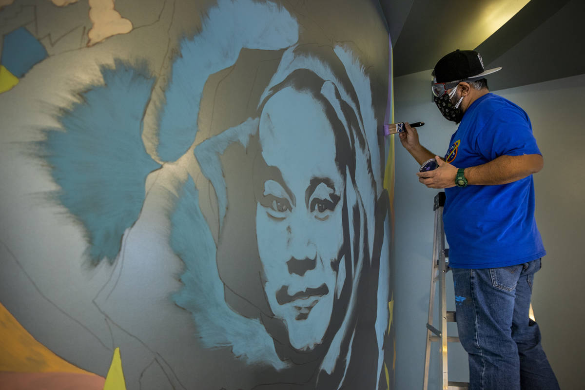 Artist Miguel Hernandez paints a mural in memory of Tony Hsieh in the lobby of ART HOUZ Theater ...