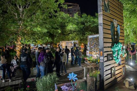 Visitors walk through the Las Vegas Community Healing Garden before the start of a ceremony hon ...