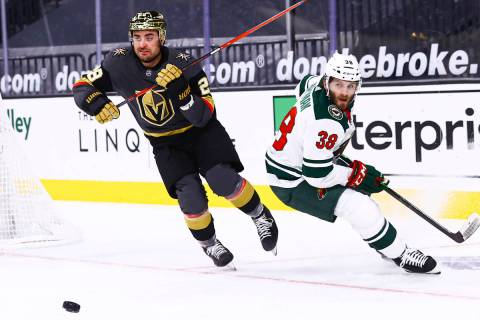 Golden Knights left wing William Carrier (28) gets the puck around Minnesota Wild right wing Ry ...