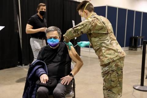 Nevada National Guard Spc. Katherine Deskins administers the Pfizer vaccine shot to Andy Perla, ...