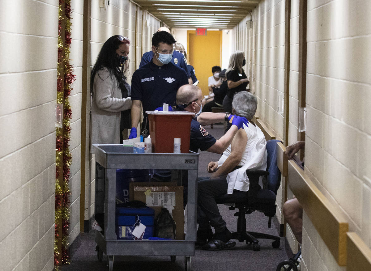 Chris Racine of Las Vegas Fire Rescue administers a COVID-19 vaccine to Hassan Ariloglu, 86, a ...