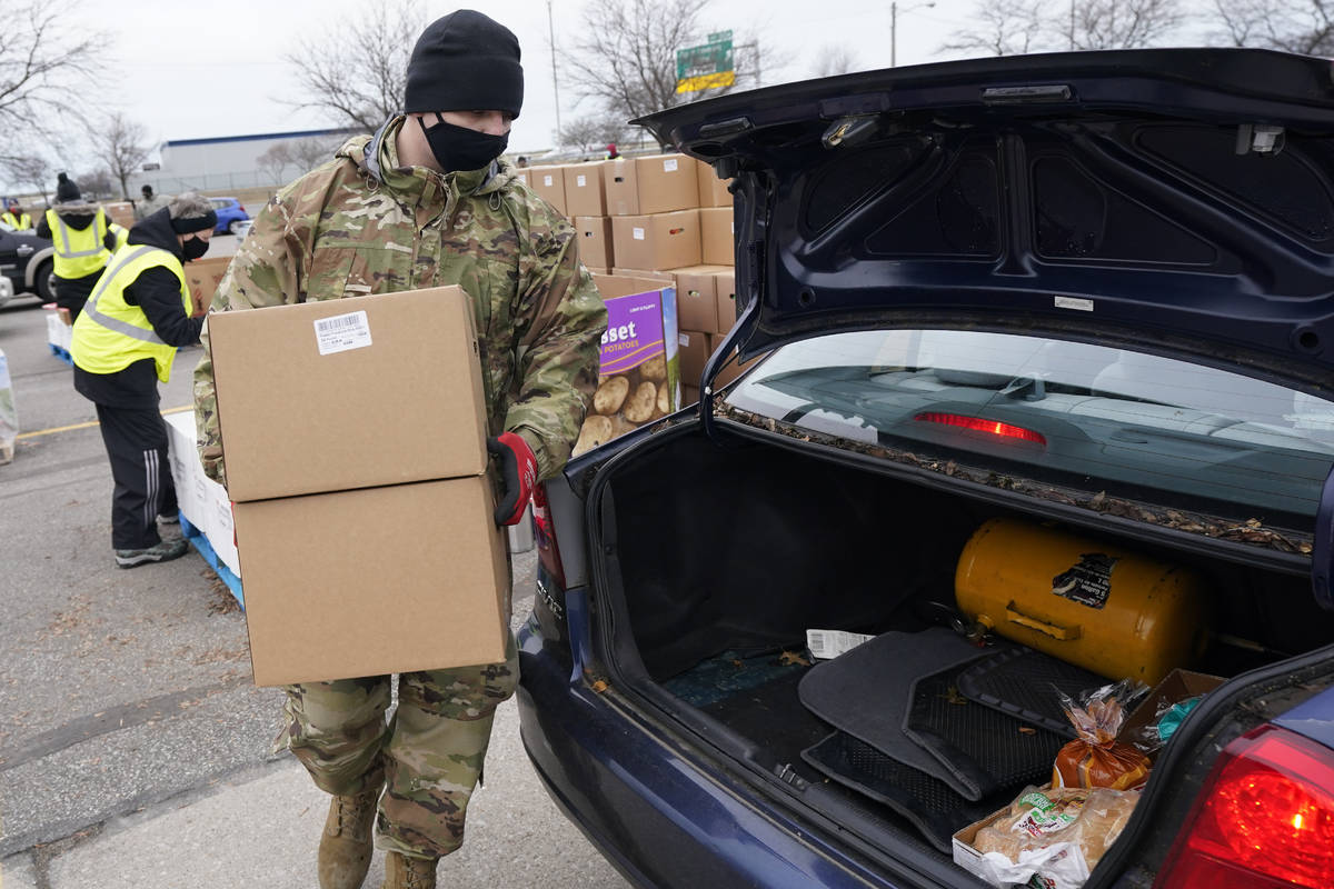 Staff Sgt. Mike Schuster loads two produce boxes into a car at a food bank distribution by the ...