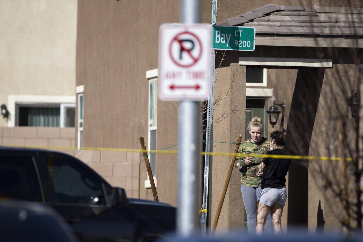 People watch outside of a home as Las Vegas police investigate an apparent murder-suicide insid ...