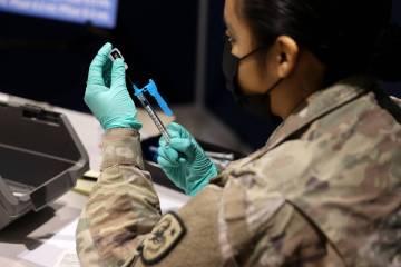 Nevada National Guard Pfc. Kimberly Hernandez prepares Pfizer vaccines at the Cashman Center CO ...