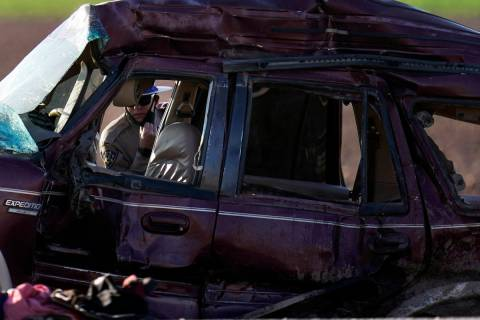 A California Highway Patrol officer examines the scene of a deadly crash in Holtville, Calif., ...