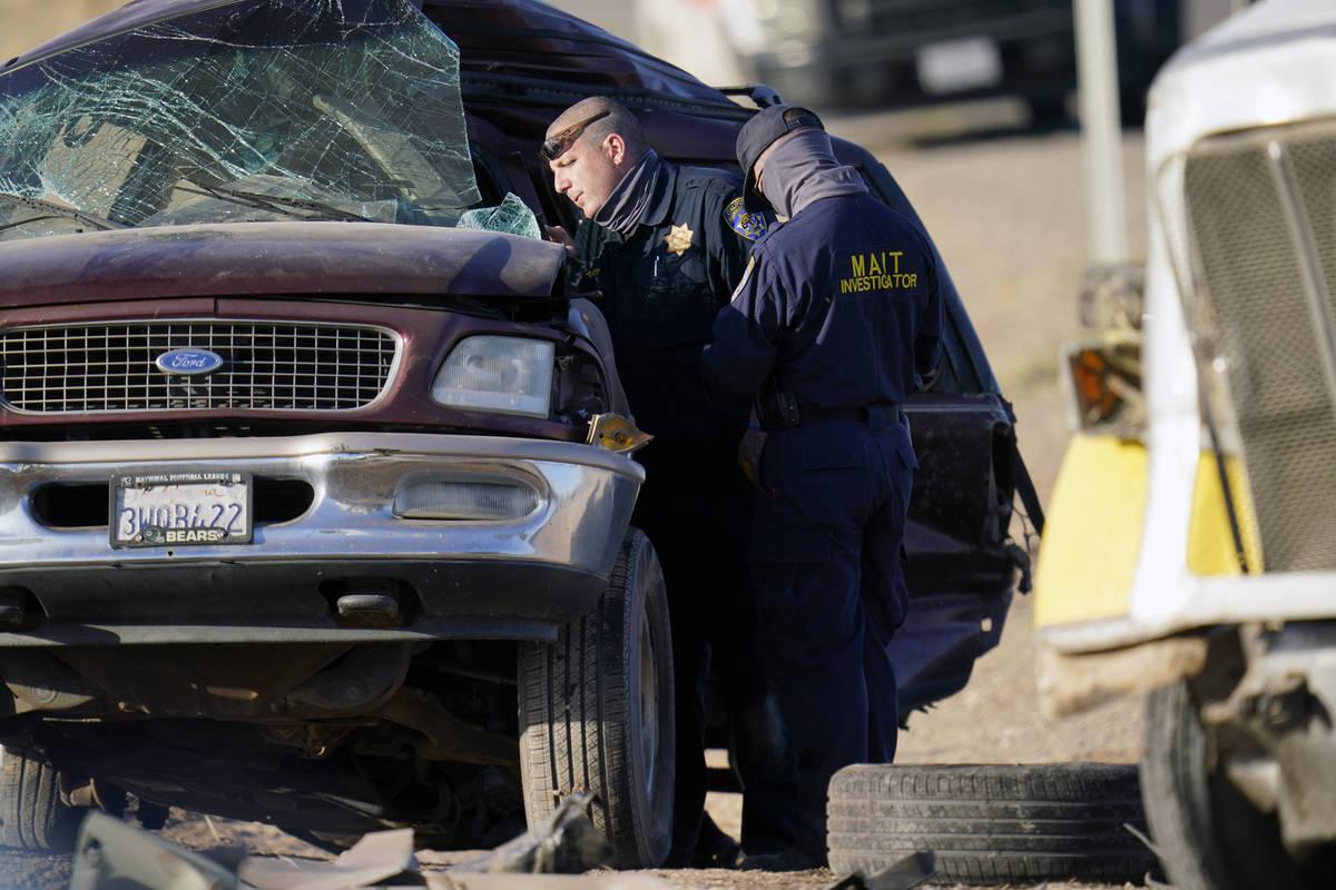 Law enforcement officers sort evidence and debris at the scene of a deadly crash in Holtville, ...