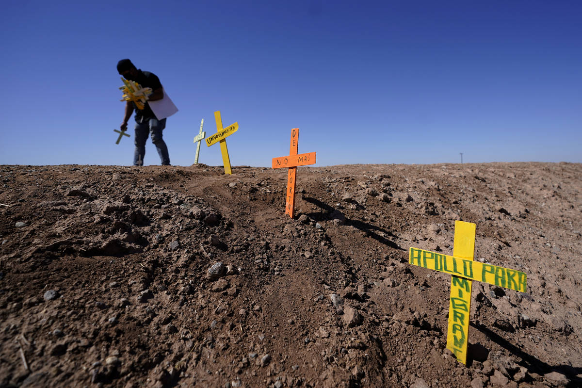 Hugo Castro leaves crosses at the scene of a deadly crash in Holtville, Calif., Tuesday, March ...