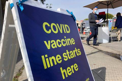 A sign is shown at a COVID-19 vaccine site in the Bayview neighborhood of San Francisco in Febr ...