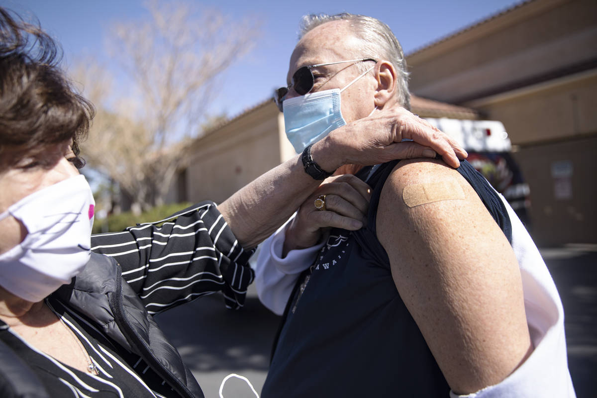 Sandra Hahnenkratt, left, shows her husband Ronald Griebell's band-aid from his vaccination sho ...