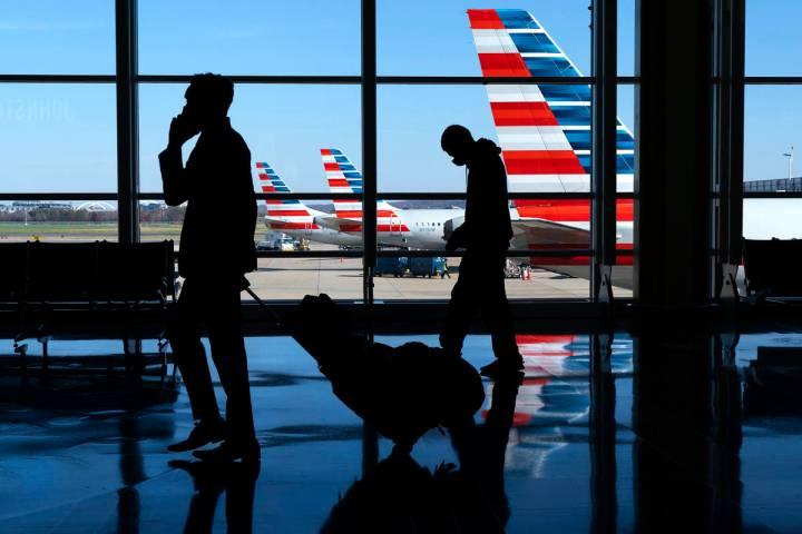 Wearing masks, travelers stroll through Reagan Washington National Airport in Arlington, Va. Ju ...