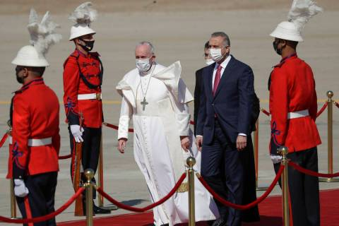 Pope Francis is flanked by Iraqi Prime Minister Mustafa al-Kadhimi upon his arrival at Baghdad' ...