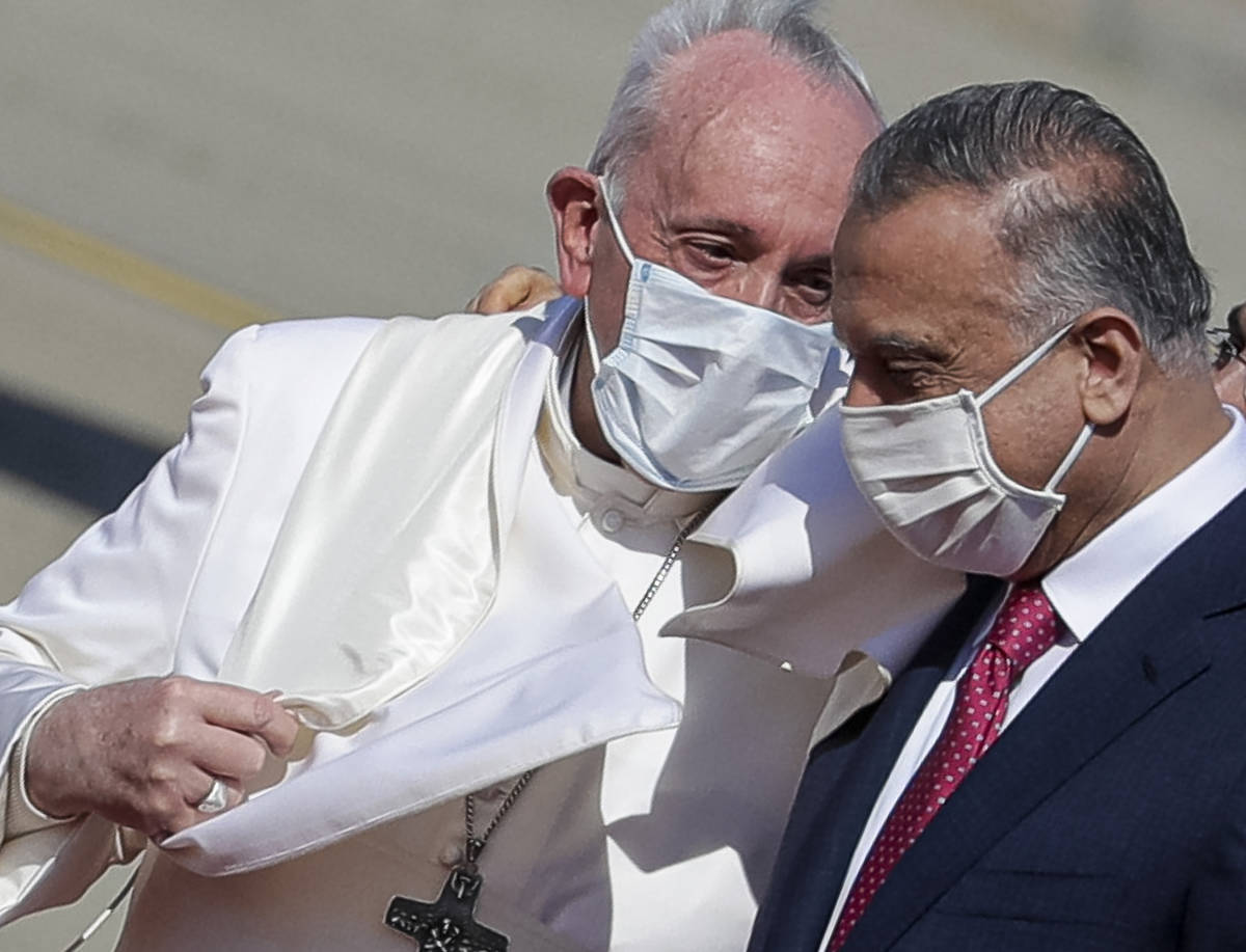 Pope Francis is greeted by Iraqi Prime Minister Mustafa al-Kadhimi as he arrives at Baghdad's i ...