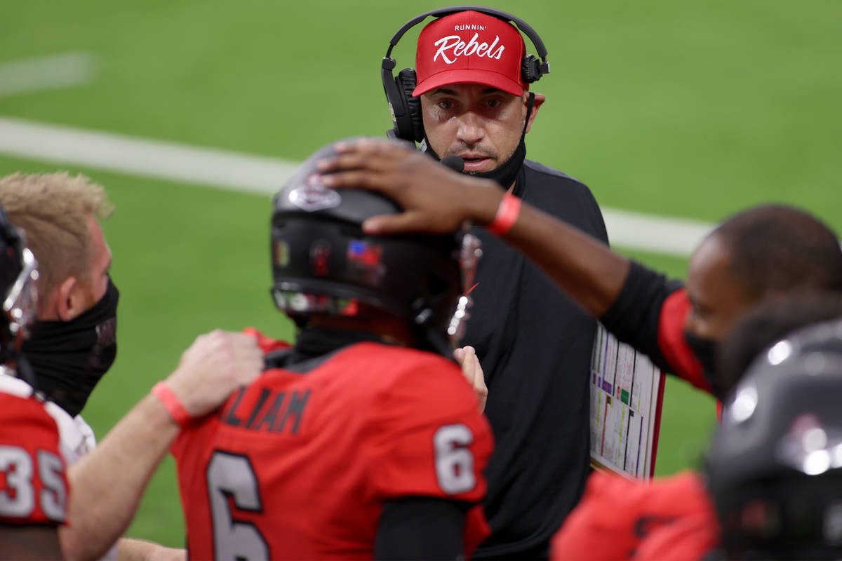 UNLV Rebels head coach Marcus Arroyo looks at quarterback Max Gilliam (6) after his rushing tou ...