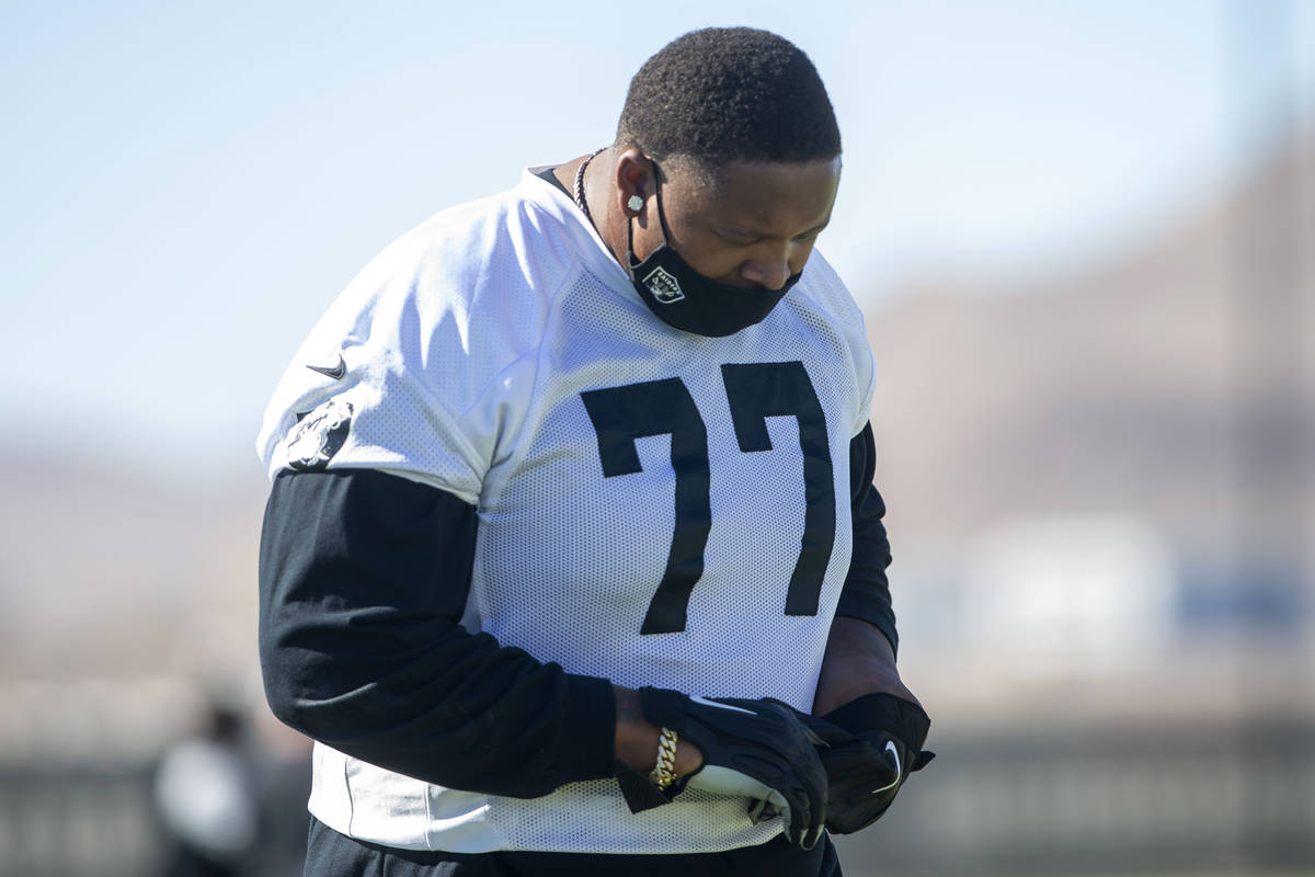 Las Vegas Raiders offensive tackle Trent Brown (77) warms up with a mask on during a practice ...