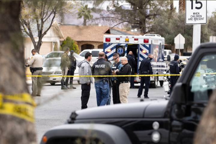 Law enforcement officers investigate a shooting near George Harris Elementary School in Las Veg ...