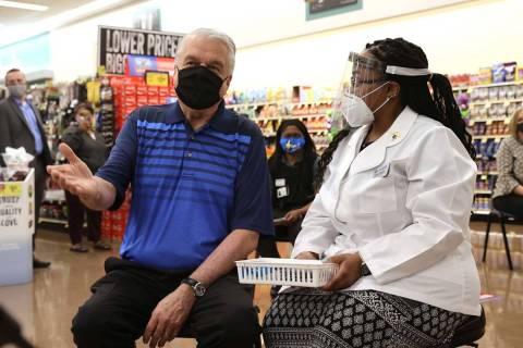 Gov. Steve Sisolak visits with Pharmacy Manager Trashelle Miro before receiving his COVID-19 va ...