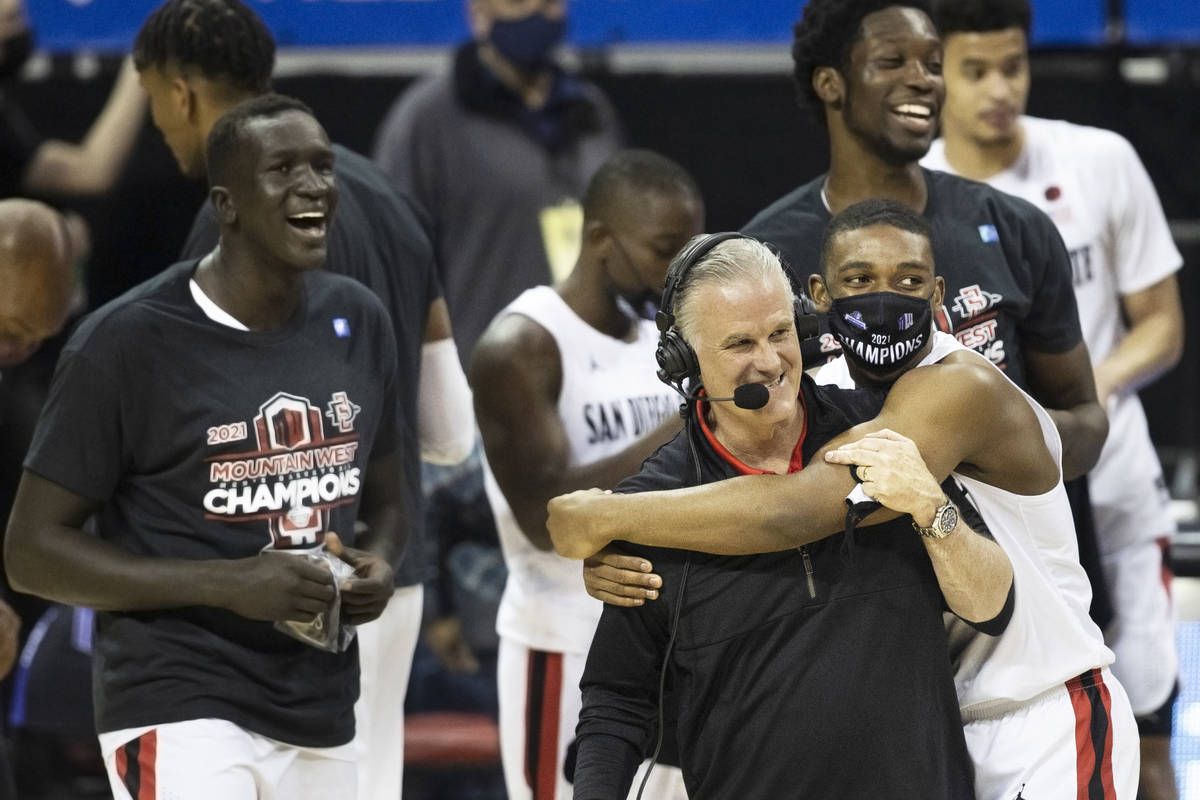 San Diego State Aztec players celebrate with head coach Brian Dutcher, right/front, after winni ...
