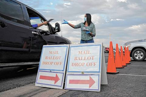 A county worker collects mail-in ballots in a drive-thru mail-in ballot drop off area at the Cl ...