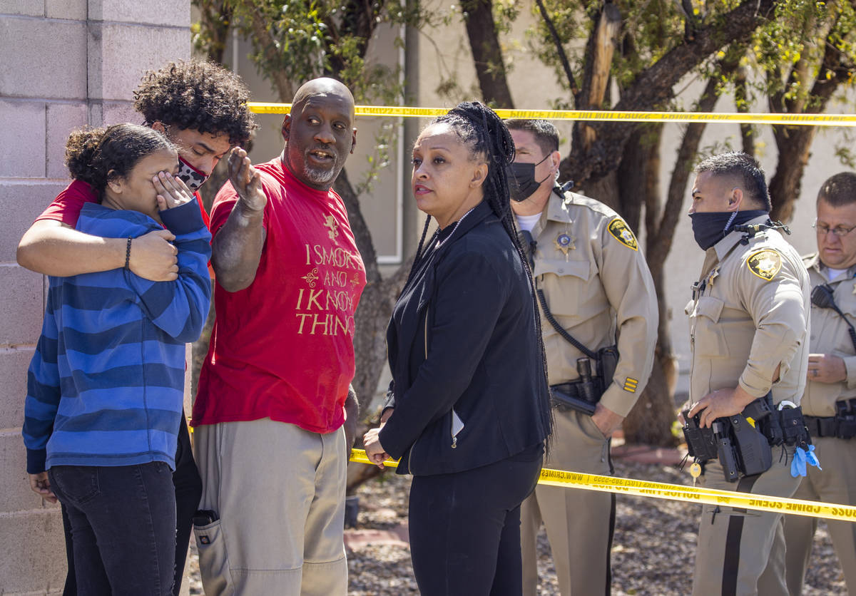 Family members converse with Metro officers near where the Clark County Fire Department works a ...